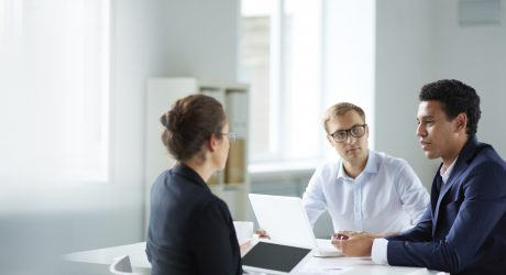 Portrait of smart business partners communicating at meeting