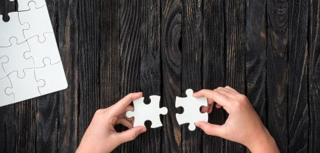 hands holding pieces of white puzzle on dark wooden table with uncompleted puzzle